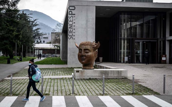 A student walks past the entrance of the Sciences-Po Grenoble's campus, in Saint-Martin-d'Heres, near Grenoble, south eastern France - JEAN-PHILIPPE KSIAZEK/AFP