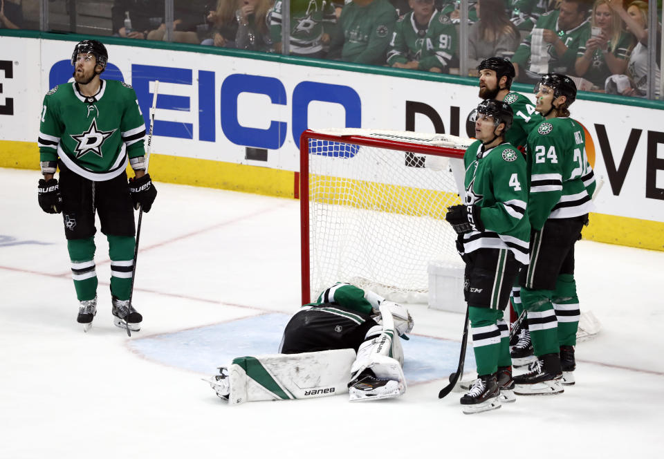 Members of the Dallas Stars look up at a replay after a shot from St. Louis Blues' Colton Parayko injured Stars goaltender Ben Bishop, laying on ice, leading to a goal by Blues' Jaden Schwartz during the third period in Game 6 of an NHL second-round hockey playoff series, Sunday, May 5, 2019, in Dallas. (AP Photo/Tony Gutierrez)