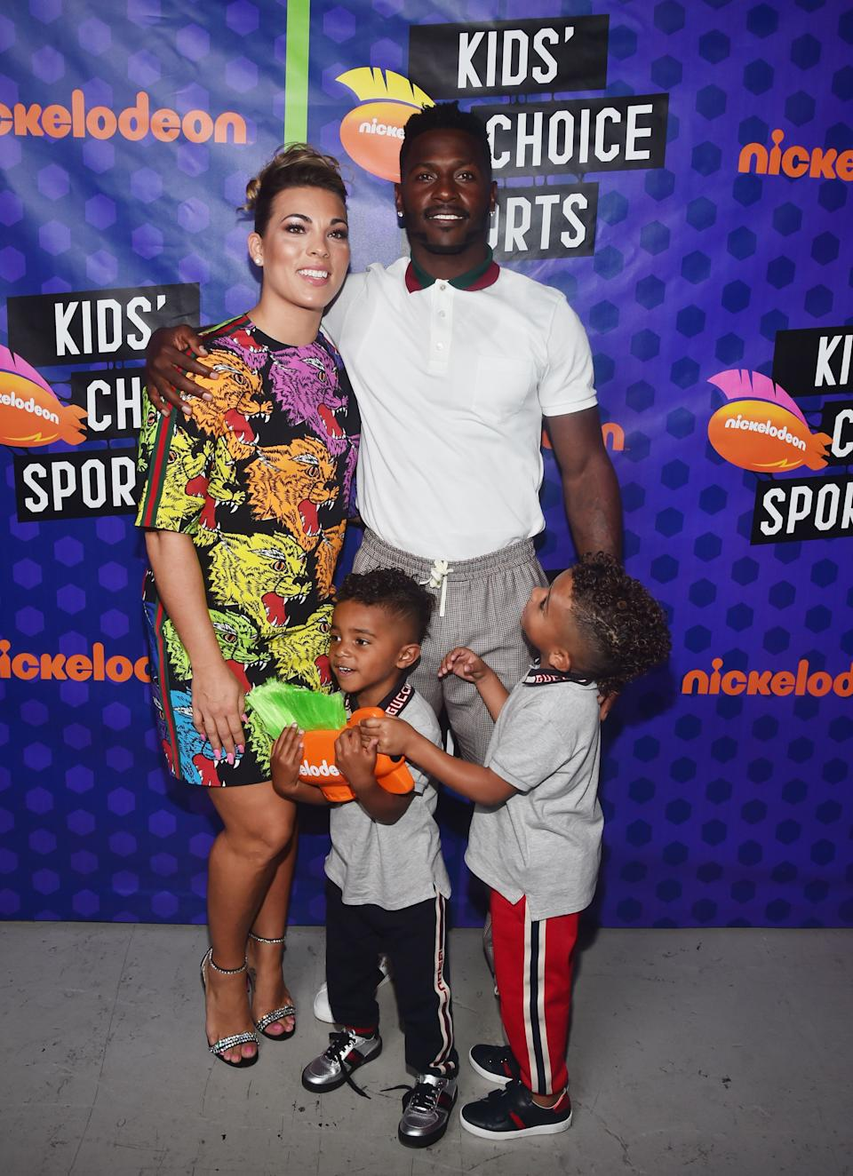 An amazing photo of Antonio Brown in a white T-shirt and grey track-suit with his ex-girlfriend, Chelsie Kyriss  in a multicolored dress and two of his sons in T-shirts and tracksuits