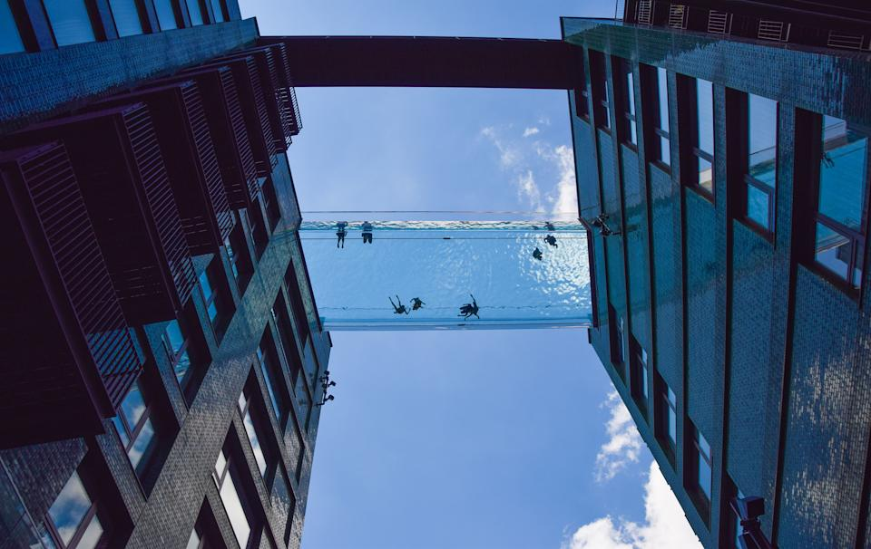 LONDON, UNITED KINGDOM - 2021/06/05: People are seen swimming in a newly opened Sky Pool in London.  A completely transparent swimming pool suspended 35 meters above ground between two apartment buildings next to the US Embassy in Nine Elms, the Sky Pool is believed to be the world's first swimming pool of its kind and is open to residents only. (Photo by Vuk Valcic/SOPA Images/LightRocket via Getty Images)