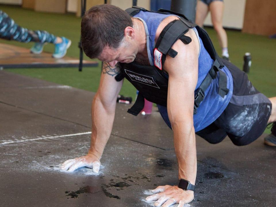 An athlete doing pushups in a weighted vest in a gym