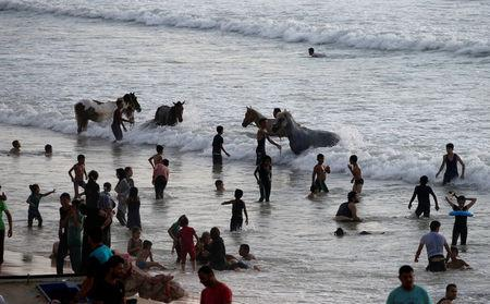 Palestinians wash horses as others swim to cool off in the Mediterranean Sea off the coast of the northern Gaza Strip July 13, 2018. REUTERS/Mohammed Salem