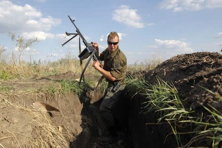 A Ukrainian serviceman with a machine gun changes his position in a trench after seeing something suspicious at a military camp in Luhansk region August 21, 2014. REUTERS/Valentyn Ogirenko