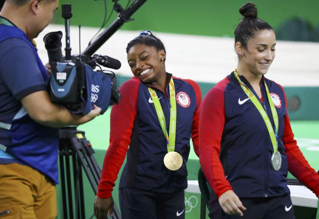 2016 Rio Olympics - Artistic Gymnastics - Victory Ceremony - Women's Individual All-Around Victory Ceremony - Rio Olympic Arena - Rio de Janeiro, Brazil - 11/08/2016. Gold medallist Simone Biles (USA) of USA and silver medallist Alexandra Raisman (USA) of USA (Aly Raisman) (R) walk with their medals during the victory ceremony after the women's individual all-around final. REUTERS/Mike Blake FOR EDITORIAL USE ONLY. NOT FOR SALE FOR MARKETING OR ADVERTISING CAMPAIGNS.