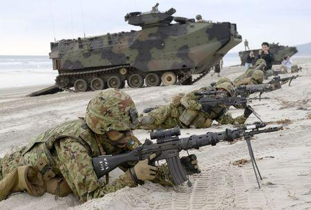 Japanese Ground Self-Defense Force's soldiers take positions after landing on the beach near U.S. Marine Corps AAV7 armored personnel vehicles (behind them) during a joint landing exercise at Marine Corps Base Camp Pendleton in California, in this February 21, 2015 file photo photo taken by Kyodo. REUTERS/Kyodo/Files