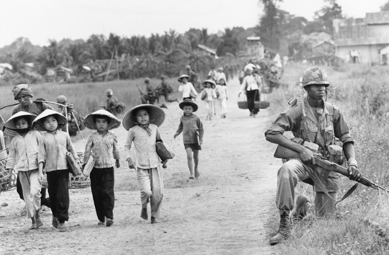 File - In this December 1965 file photo shot by Associated Press photographer Horst Faas, a U.S. 1st Division soldier guards Route 7 as Vietnamese women and school children return home to the village of Xuan Dien from Ben Cat, Vietnam. Faas, a prize-winning combat photographer who carved out new standards for covering war with a camera and became one of the world's legendary photojournalists in nearly half a century with The Associated Press, died Thursday May 10, 2012. He was 79. (AP Photo/Horst Faas)