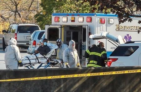 Ambulance workers wearing protective gear load a patient with possible Ebola symptons into the back of an ambulance at the Harvard Vanguard facility in Braintree, Massachusetts October 12, 2014 in this still image from video.  REUTERS/Kevin Wiles Jr.