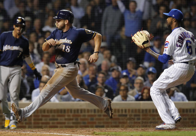 Milwaukee Brewers' Mike Moustakas comes in to score on a wild pitch by Chicago Cubs' Carl Edwards Jr., right, during the sixth inning of a baseball game Monday, Sept. 10, 2018, in Chicago. (AP Photo/Jim Young)