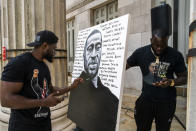 Artist Dennis Owes, 31, from Ghana gives the last touch to his portrait of George Floyd during a rally on Sunday, May 23, 2021, in Brooklyn borough of New York. George Floyd, whose May 25, 2020 death in Minneapolis was captured on video, plead for air as he was pinned under the knee of former officer Derek Chauvin, who was convicted of murder and manslaughter in April 2021. (AP Photo/Eduardo Munoz Alvarez)