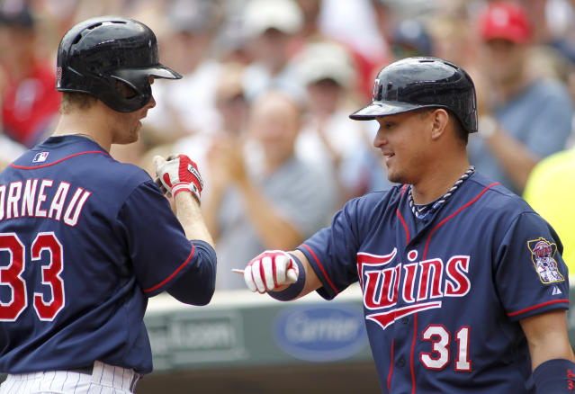 Minnesota Twins Justin Morneau is congratulated by Oswaldo Arcia after home run in the first inning of their baseball game in Minneapolis, Sunday, Aug. 4, 2013. (AP Photo/Andy Clayton-King)