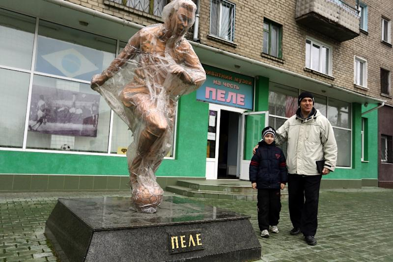 A man poses with his child next to the Pele sculpture outside the museum dedicated to the retired Brazilian football player in the eastern Ukrainian city of Lugansk (AFP Photo/Aleksey Filippov)