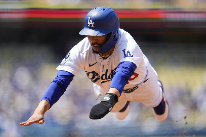 Los Angeles Dodgers' Mookie Betts (50) dives back to first base safely during the third inning of a baseball game against the Arizona Diamondbacks Sunday, July 11, 2021, in Los Angeles. (AP Photo/Ashley Landis)