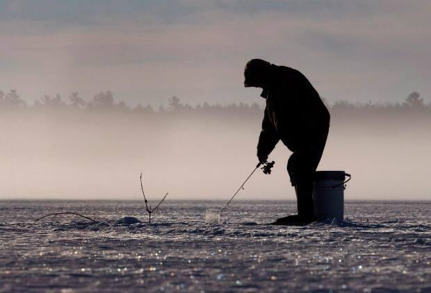 Someone ice fishing on Pigeon Lake in the Kawarthas region in February 2017. People can still fish for what's in season, but they can't do it out of a hut after certain dates this month. (Fred Thornhill/Canadian Press - image credit)