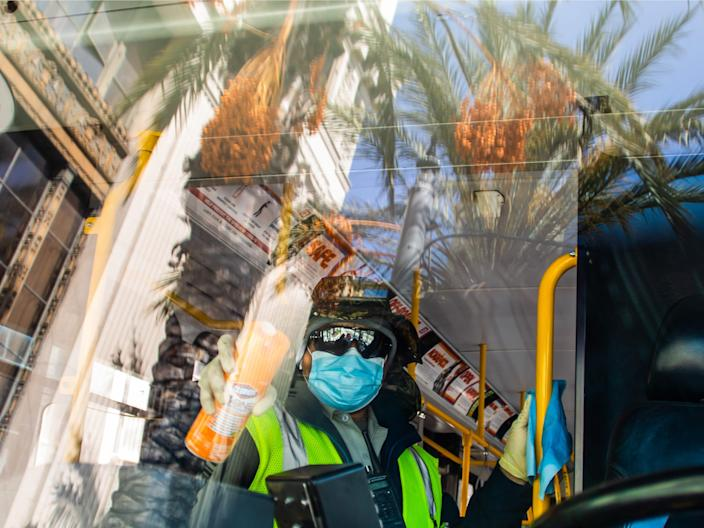 Long Beach Transit Worker, Mateo Alvorado, disinfects a bus in Long Beach, California on April 2, 2020. APU GOMES:AFP via Getty Images)