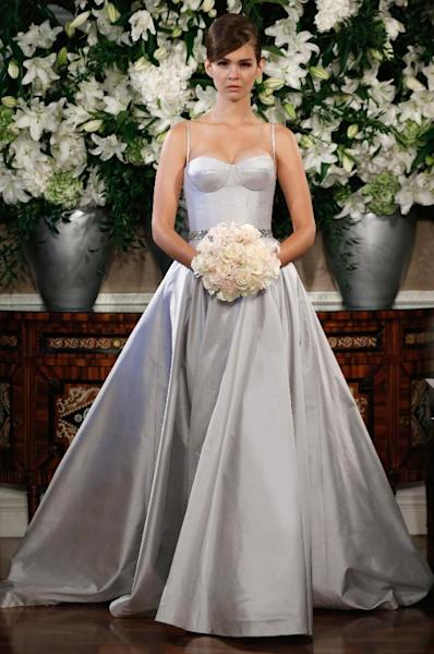 This photo released by Romona Keveza shows a sleeveless Romona Keveza Coutour wedding dress. The traditional bridal gown isn't a skimpy silhouette: It's long and typically without a plunging neckline or high slit. There's often a whole lot of fabric. One of the few opportunities for brides to be a little bare is to go with a strapless or sleeveless dress. New bridal collections are dominated by dresses with no sleeves. (AP Photo/Romona Keveza)