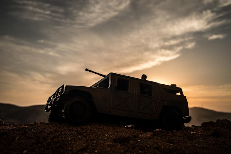 Military patrol car with sunset in the background.