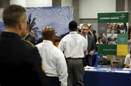"Lockheed Martin talent acquisition manager Charles Tulaney (R) greets job applicants at a U.S. Chamber of Commerce Foundation ""Hiring Our Heroes"" military job fair in Washington January 8, 2016. REUTERS/Gary Cameron"