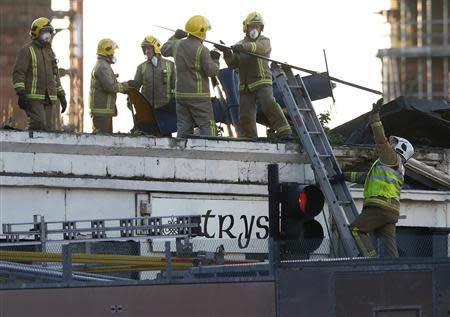 Rescue workers lift a rotor blade from the site of a police helicopter crash onto the Clutha Pub in central Glasgow, Scotland