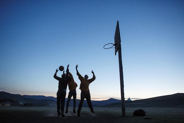 "Young Buddhist monks play basketball at dusk outside the Amarbayasgalant Monastery in the Baruunburen district, Selenge province, Mongolia, April 25, 2018. REUTERS/Thomas Peter SEARCH ""MILLENNIAL MONKS"" FOR THIS STORY. SEARCH ""WIDER IMAGE"" FOR ALL STORIES."