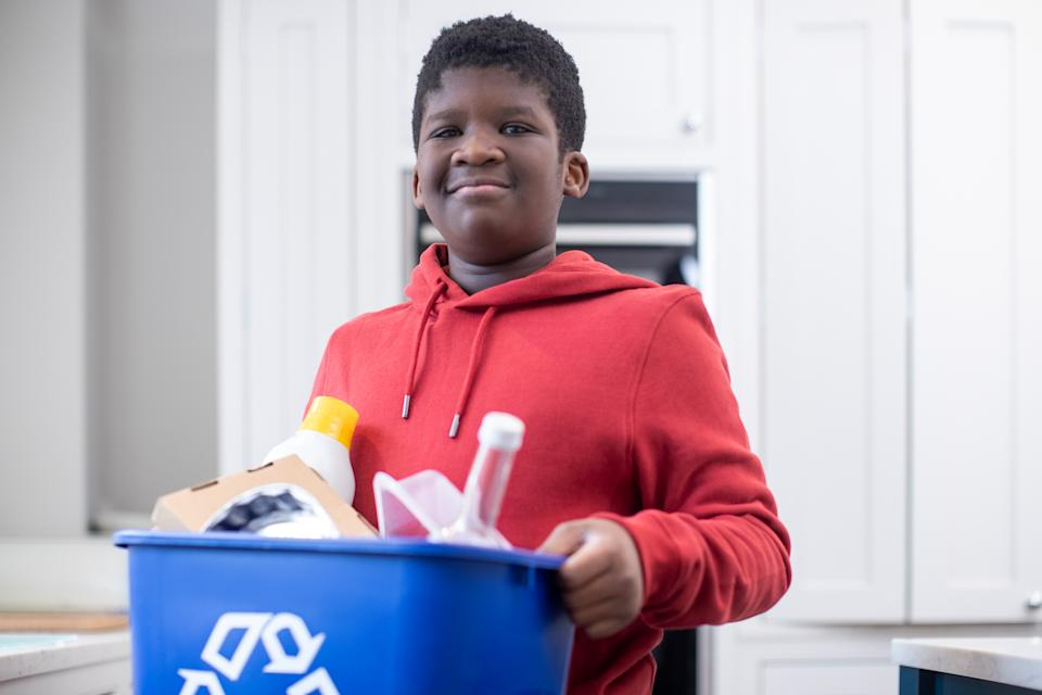Portrait Of Boy Standing In Kitchen At Home Carrying Recycling Bin