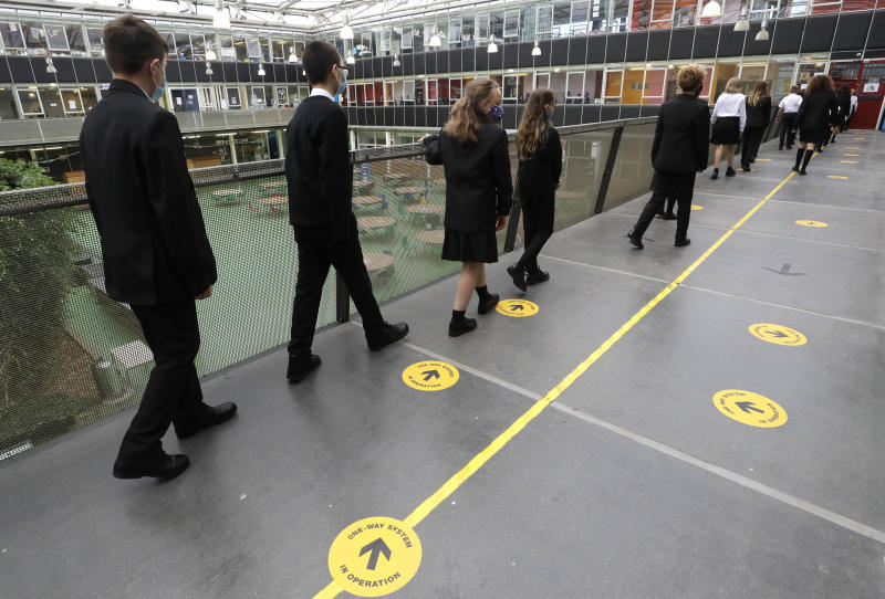 Pupils follow social distancing signs as they walk along a corridor at Kingsdale Foundation School in London, Thursday, Sept. 3, 2020. Schools in England are starting to reopen with special measures in place to deal with Coronavirus. (AP Photo/Kirsty Wigglesworth)