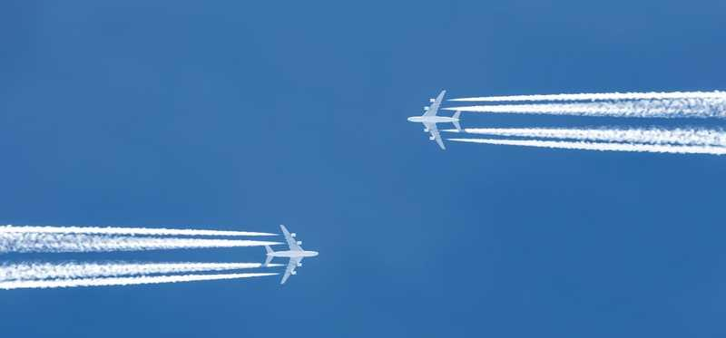 Two planes flying in opposite directions, passing each other in the air.