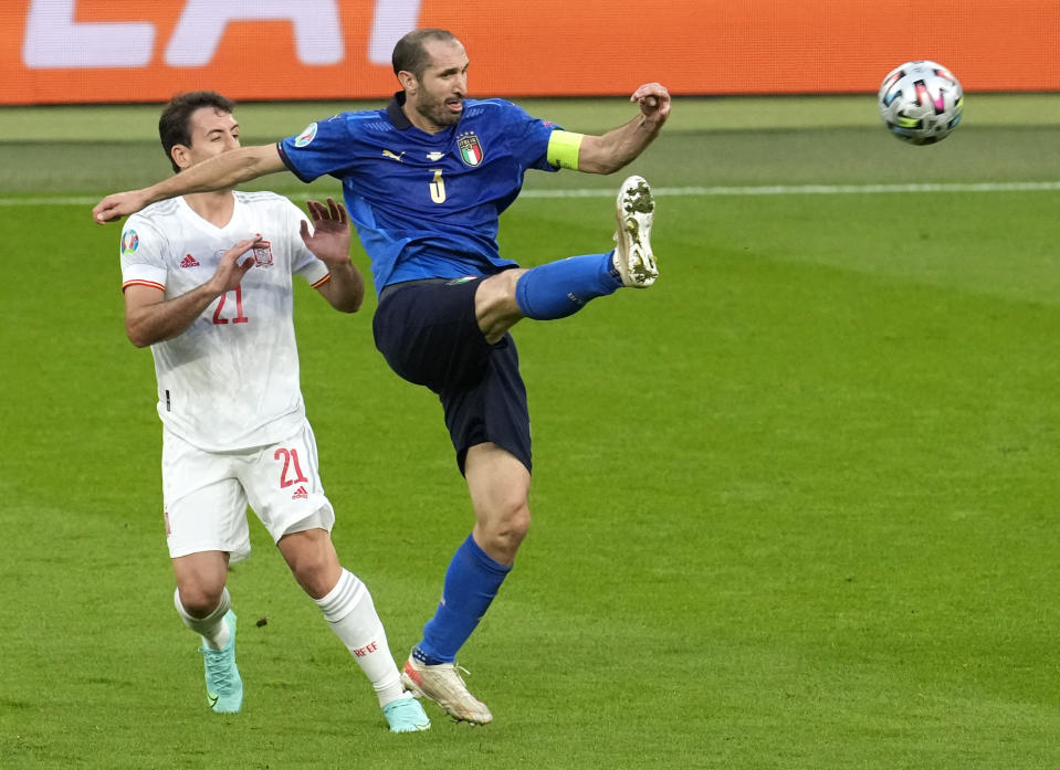 Italy's Giorgio Chiellini, right, and Spain's Mikel Oyarzabal battle for the ball during the Euro 2020 soccer championship semifinal between Italy and Spain at Wembley stadium in London, Tuesday, July 6, 2021. (AP Photo/Matt Dunham,Pool)