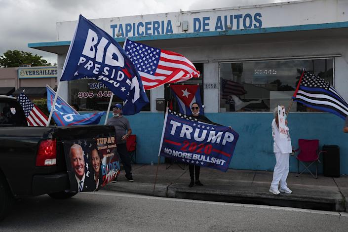 A caravan of supporters for Democratic presidential nominee Joe Biden drive past supporters of President Donald Trump standing on the sidewalk next to the Versailles Restaurant during a Worker Caravan for Biden event on Sunday in Miami.