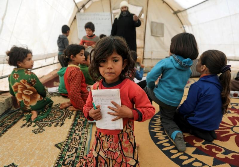 A student holds a notebook as she sits at a makeshift school in a tent in Azaz