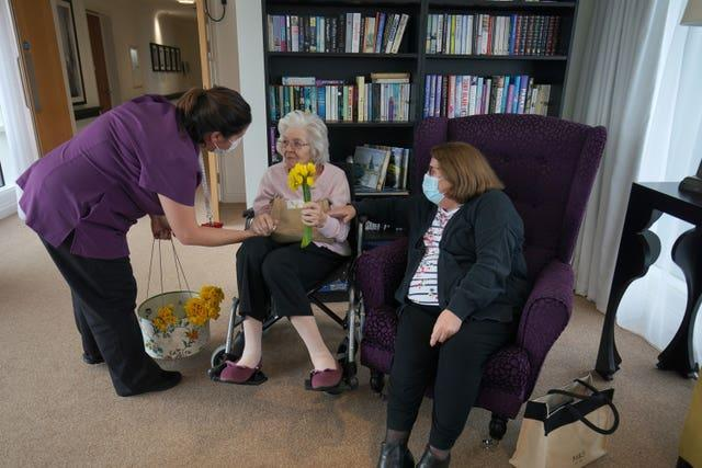 A member of staff gives a bunch of daffodils to Sylvia Newsom