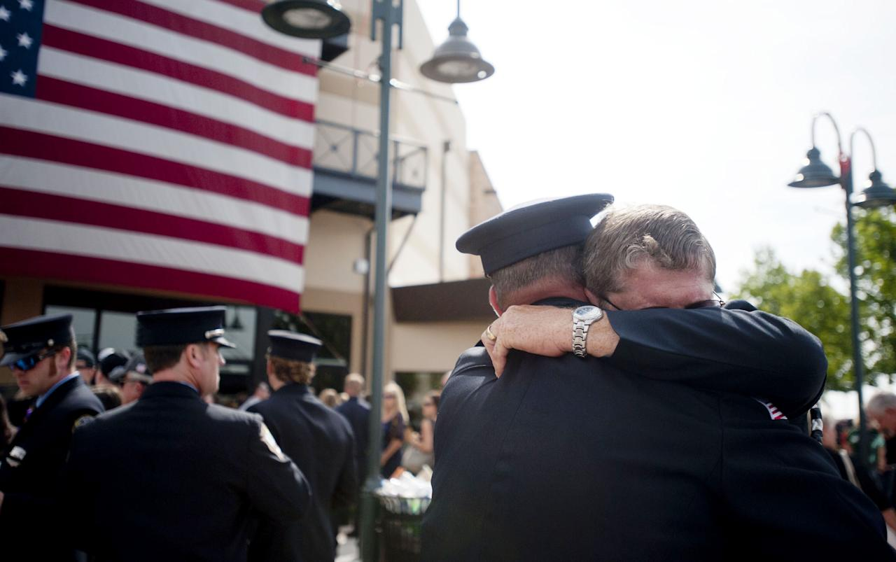 PRESCOTT VALLEY, AZ-JULY 9: Chaplain Bob Ossler (R) with the Mayer, Arizona fire department hugs people at the entrance to a memorial service honoring the 19 firefighters killed in a wildfire at Tim's Toyota Center July 9, 2013 in Prescott Valley, Arizona. The firefighters, of the Granite Mountain Hotshots crew, died battling the fast-moving blaze on June 30. (Photo by Laura Segall/Getty Images)