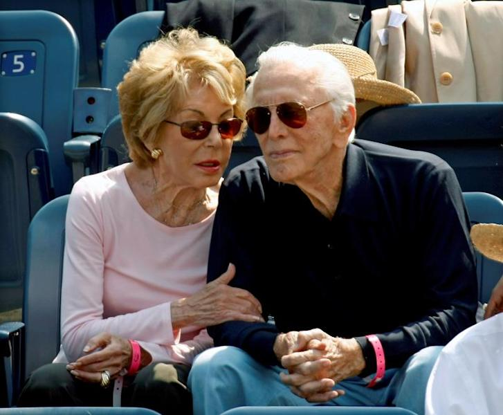US actor Kirk Douglas (R) sits with his wife Anne Buydens (L) as they watch Novak Djokovic of Serbia playing against David Ferrer of Spain during the first men's semifinal match on the thirteenth day of the 2007 US Open tennis tournament in Flushing Meadows, New York, USA, 08 September 2007 (reissued 05 February 2020). EFE/Andrew Gomber/Archivo