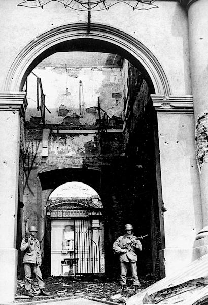 FILE - In this Sept. 11, 1973 file photo, soldiers stand guard at the main entrance of La Moneda presidential palace after it was bombed during a military coup led by Gen. Augusto Pinochet that brought down the government of President Salvador Allende in Santiago, Chile. On Sept. 11, 2013, Chile marks the 40th anniversary of the coup. (AP Photo/El Mercurio, File) CHILE OUT - NO PUBLICAR EN CHILE