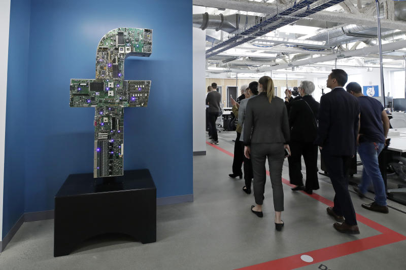 FILE - In this Jan. 9, 2019, file photo, media and guests tour Facebook's new 130,000-square-foot offices, which occupy the top three floors of a 10-story Cambridge, Mass., building. Facebook unveiled a broad plan Tuesday, June 18, to create a new digital currency. (AP Photo/Elise Amendola, File)