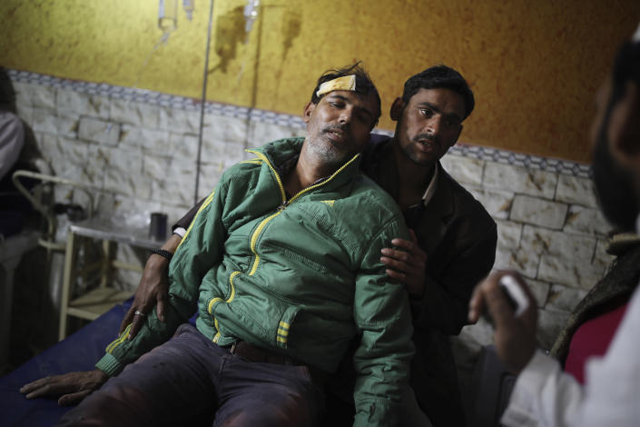 In this Friday, Feb. 28, 2020 photo, an unidentified relative supports Mehdi Hassan, who was hit by an iron rod by rioters, as he is treated at Al-Hind hospital in Old Mustafabad neighborhood of New Delhi, India.As the Mustafabad neighborhood of India's capital broke out in brutal communal riots for three days this week, the Al-Hind Hospital turned from a community clinic into a trauma ward. Authorities haven't said what sparked the violence that has left more than 40 dead and hundreds injured, but it was the culmination of growing tensions since the passage of a citizenship law in December that fast-tracks naturalization for some religious minorities from neighboring countries but not Muslims. (AP Photo/Altaf Qadri)