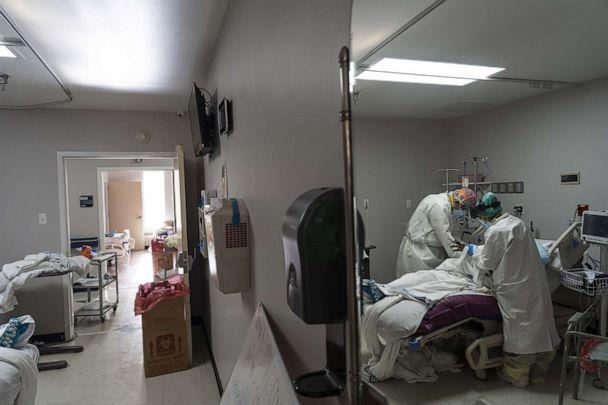 PHOTO: Medical staff wearing full PPE change a patient's clothes in the COVID-19 intensive care unit at the United Memorial Medical Center on June 30, 2020, in Houston. (Go Nakamura/Getty Images)
