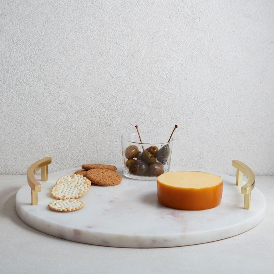 <p>Or if you prefer a round option, go for this polished <span>Marble &amp; Brass Round Cheese Board</span> ($50).</p>