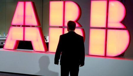 FILE PHOTO: FILE PHOTO: A man stands in front of the logo of Swiss engineering group ABB in Zurich