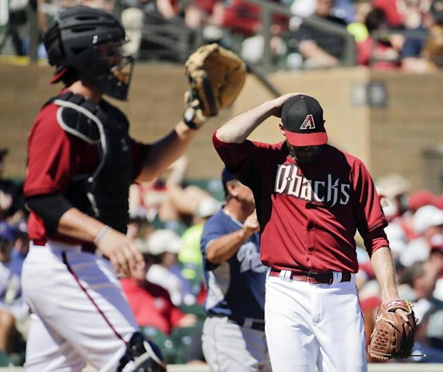 Arizona Diamondbacks relief pitcher Bo Schultz, right, walks back to the mound after giving up a run to the San Diego Padres as catcher Tuffy Gosewisch waits for the ball during the first inning of a spring training baseball game in Scottsdale, Ariz., Sunday, March 9, 2014. (AP Photo/Chris Carlson)