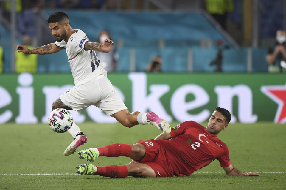 Italy's Lorenzo Insigne, left, is challenged by Turkey's Zeki Celik during the Euro 2020 soccer championship group A match between Italy and Turkey at the Olympic stadium in Rome, Friday, June 11, 2021. (Alberto Lingria/Pool Photo via AP)