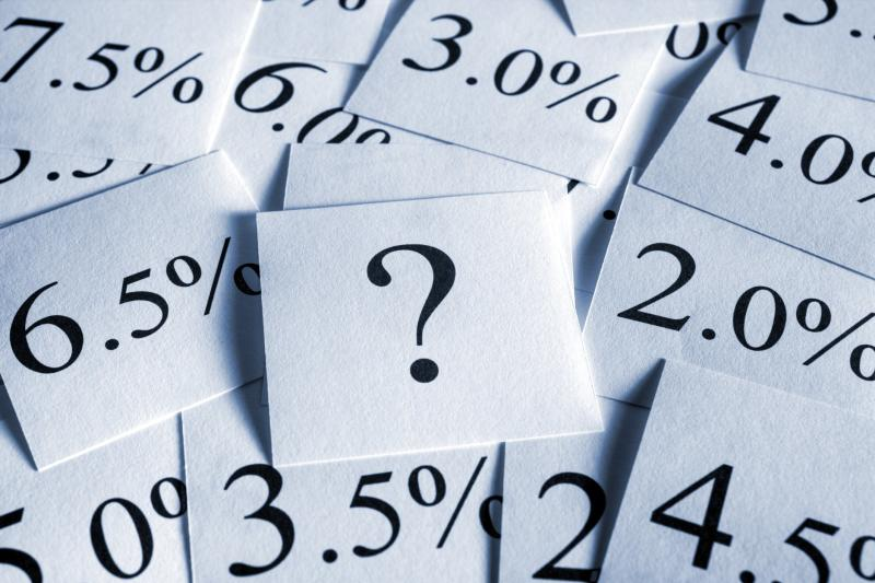 A question mark and different percentage rates printed on note cards in a messy pile.
