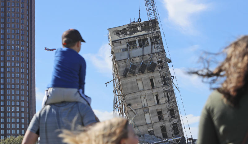 "People gather to watch the demolition of the so called ""Leaning Tower of Dallas"" as a wrecking ball works to topple the structure north of downtown Dallas, Monday, Feb. 24, 2020. The still standing structure is part of an 11-story building that found a second life online after surviving a first demolition attempt. The former Affiliated Computer Services building inspired jokes and comparisons to Italy's Leaning Tower of Pisa when a Feb. 16 implosion failed to bring down its core. The company that engineered the blast said some explosives did not go off. (AP Photo/LM Otero)"