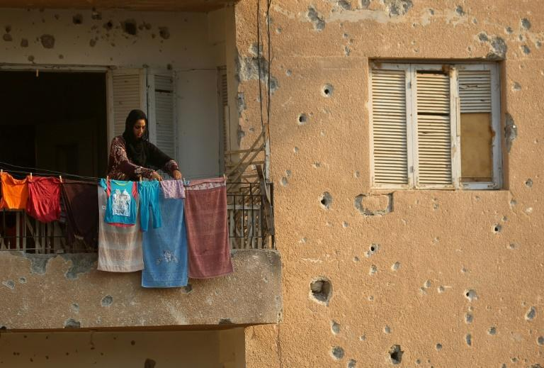 A displaced woman who fled the Islamic State group's Syrian stronghold of Raqa hangs laundry at a shrapnel riddled abandoned building in the town of Tabqa