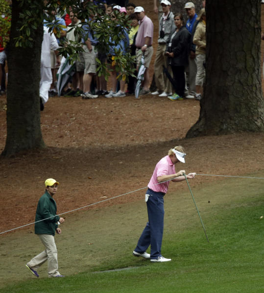 Brandt Snedeker removes a spectator rope before hitting out of the rough off the 10th fairway during the fourth round of the Masters golf tournament Sunday, April 14, 2013, in Augusta, Ga. (AP Photo/David J. Phillip)