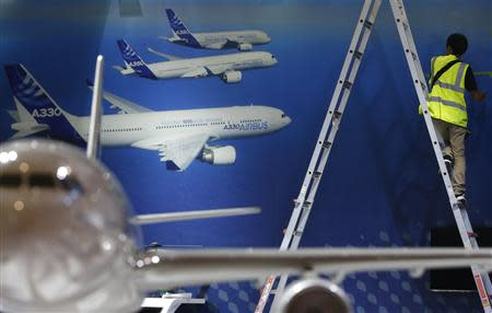 A worker makes final touches to the Airbus booth ahead of the Singapore Airshow