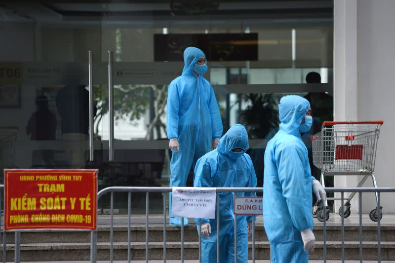 Medical workers in protective suits stand outside a quarantined building amid the coronavirus disease outbreak in Hanoi