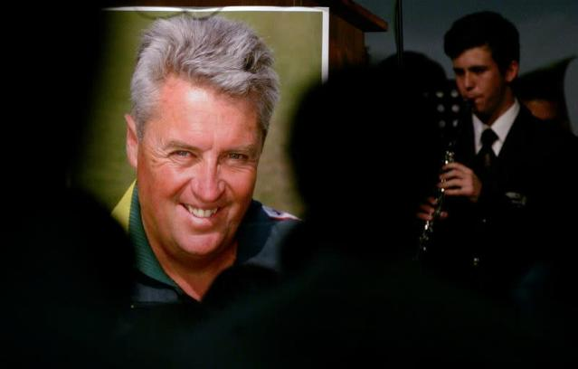 FILE PHOTO: A schoolboy plays a musical instrument beside a poster of Pakistan cricket coach Bob Woolmer during his memorial service in Cape Town