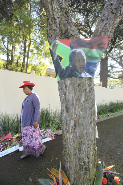 A woman walks past a tree with a South African flag bearing the portrait of former president Nelson Mandela outside his house in Johanesburg, South Africa,Tuesday, July, 2, 2013. Mandela remains in a critical condition in a hospital in Pretoria. (AP Photo/Tsvangirayi Mukwazhi)