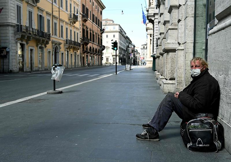 Image: A homeless man sits in Via del Corso in Rome (Vincenzo Pinto / AFP - Getty Images)