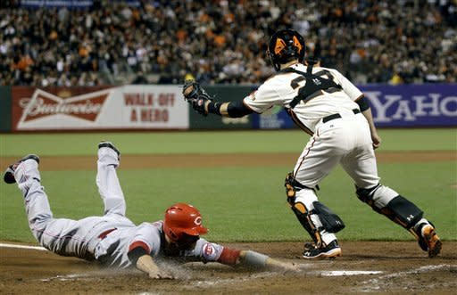 Cincinnati Reds' Joey Votto slides into home to score on a single hit by Scott Rolen in the fourth inning as San Francisco Giants catcher Buster Posey, right, attempts to tag him during Game 2 of the National League division baseball series in San Francisco, Sunday, Oct. 7, 2012. (AP Photo/Marcio Jose Sanchez, pool)